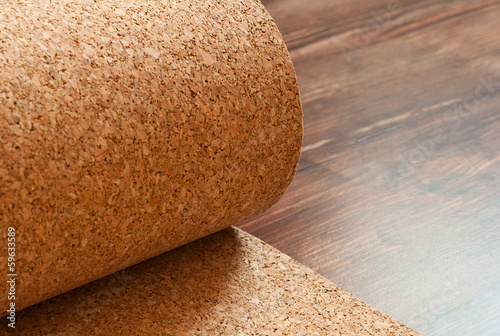 Roll of cork lies on a brown floor - 59633589