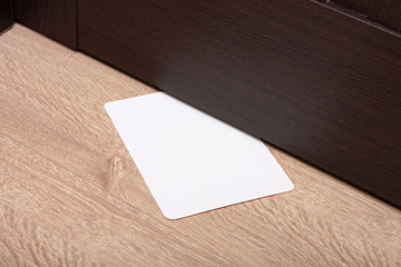 white envelope with message slipped under wooden door. Blank