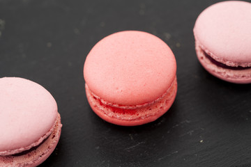 Pink macaroons in a row on black background