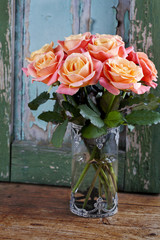 Bouquet of beautiful roses in vase on wooden background
