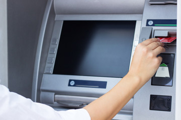Woman put her credit card at the ATM