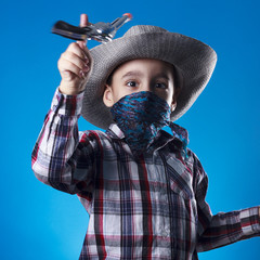 Masked little cowboy with revolver toy