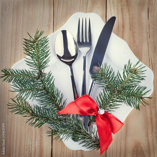 Christmas cutlery and fir tree on wooden background