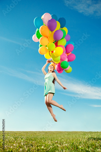 Luxury fashion woman with balloons in hand on the field against