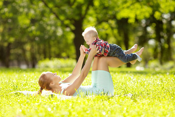 Cute little baby in the park with mother on the grass. Sweet bab