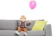 Cute little boy sitting on sofa with a balloon