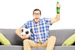 Excited male sport fan with soccer ball and beer watching sport