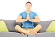 Guy meditating seated on a sofa