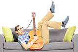 Excited young male lying on a modern couch and playing a guitar