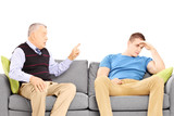 Father reprimending his son seated on a modern sofa