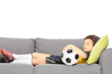 Boy in sportswear with a football sleeping on a modern sofa