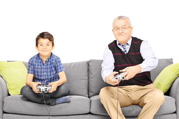 Grandfather with his nephew seated on a modern sofa playing