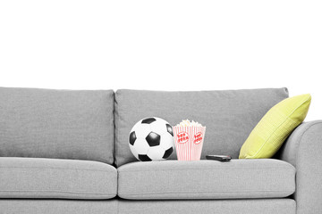 Studio shot of a couch with soccer ball and popcorn box on it