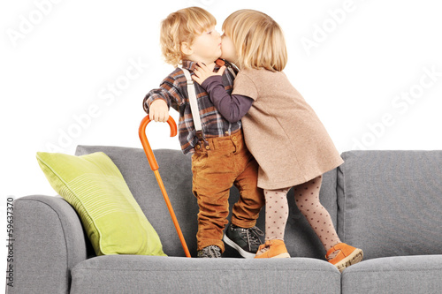 Girl kissing a boy while standing on a  modern sofa