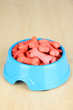 Dry dog food in bowl on wooden background