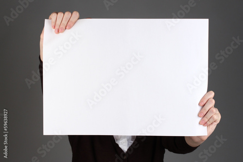 Woman holding blank sign in front her face, on color background