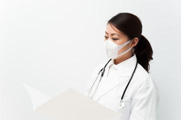 カルテを見ている白衣の看護婦