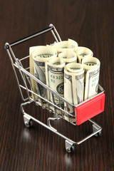 Shopping trolley with dollars, on dark background