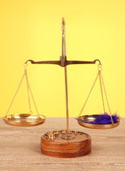 Balance scale with feather on table on yellow background