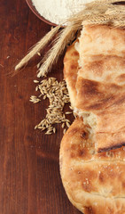 Pita breads with spikes and flour on wooden background