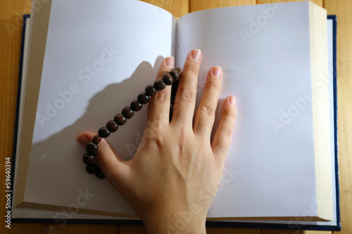 Hands with rosary and holy book, on light background