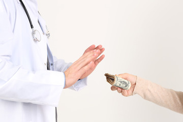 Male Doctor receiving money from patient, isolated on white