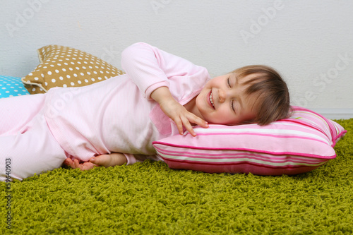 Little girl lying on carpet in room