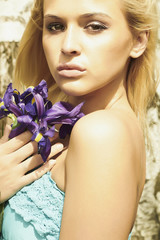Beautiful blond woman with flowers in forest.summer blue flower