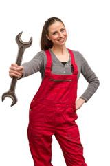 Frau im Blaumann mit Schraubenschlüssel