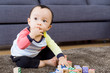 Asian baby boy with fingers in mouth at living room