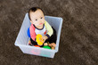 Asian baby boy playing inside the plastic box
