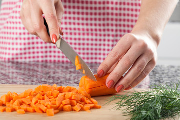 Woman chopping carrot