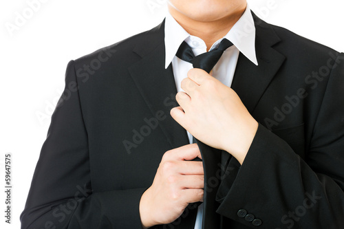 Businessman adjusting tie isolated on white