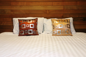 Pillow on white bed in wooden bedroom