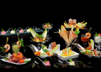 Various elegant gourmet dishes on black background