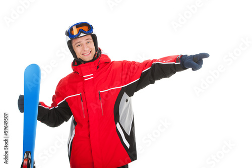 Smiling active man with ski pointing on empty space.