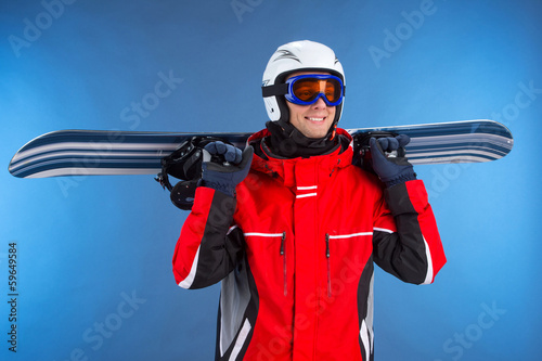 Smiling happy sportsman holding snowboard over shoulder.