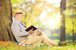Senior gentleman sitting on a grass and reading a novel in park