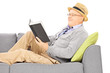 Senior man with hat on a sofa reading a novel