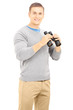 Smiling casual man holding a binocular and looking at camera