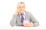 Middle aged man posing on a table with piggy bank