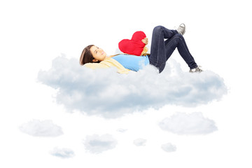 Smiling girl with red heart in her hand lying on clouds