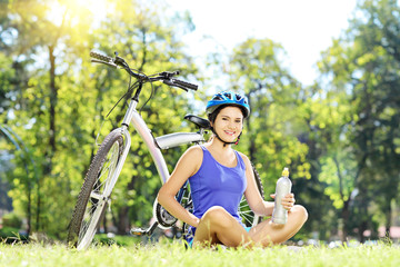 Young female biker sitting on a grass next to her bike in a park