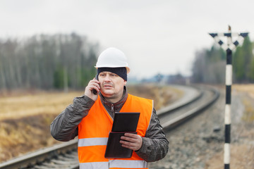 Railroad employee with phone  tablet PC