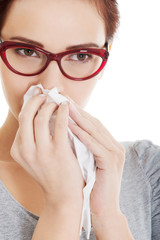Young beautiful woman having runny nose, with tissue.