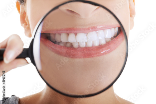 Beautiful woman with magnifying glass showing her perfect white