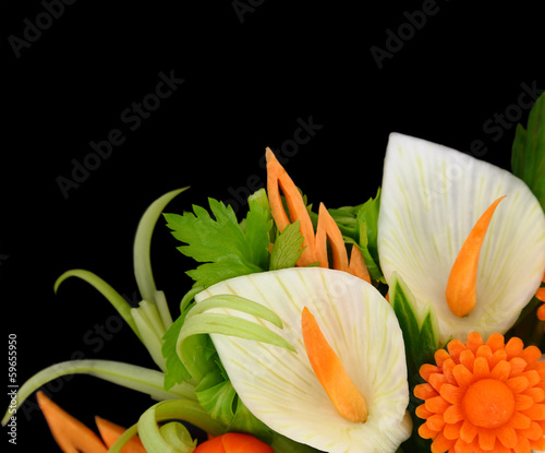 Flowers carved from fruits and vegetables on black background