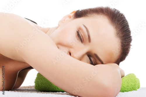 Beautiful young woman lying and relaxing during stone masasge.
