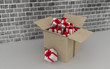 Cardboard box with gifts on brick wall background.