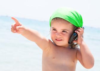 Bambina al mare con telefono